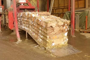 """<div class=""""bildtext_en"""">5 The waste cardboard is pressed into large bales so that it can be transported to the customer in a space-saving manner</div>"""