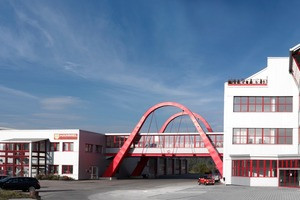 "<div class=""bildtext_en"">Company buildings with the mentioned red bridge</div>"